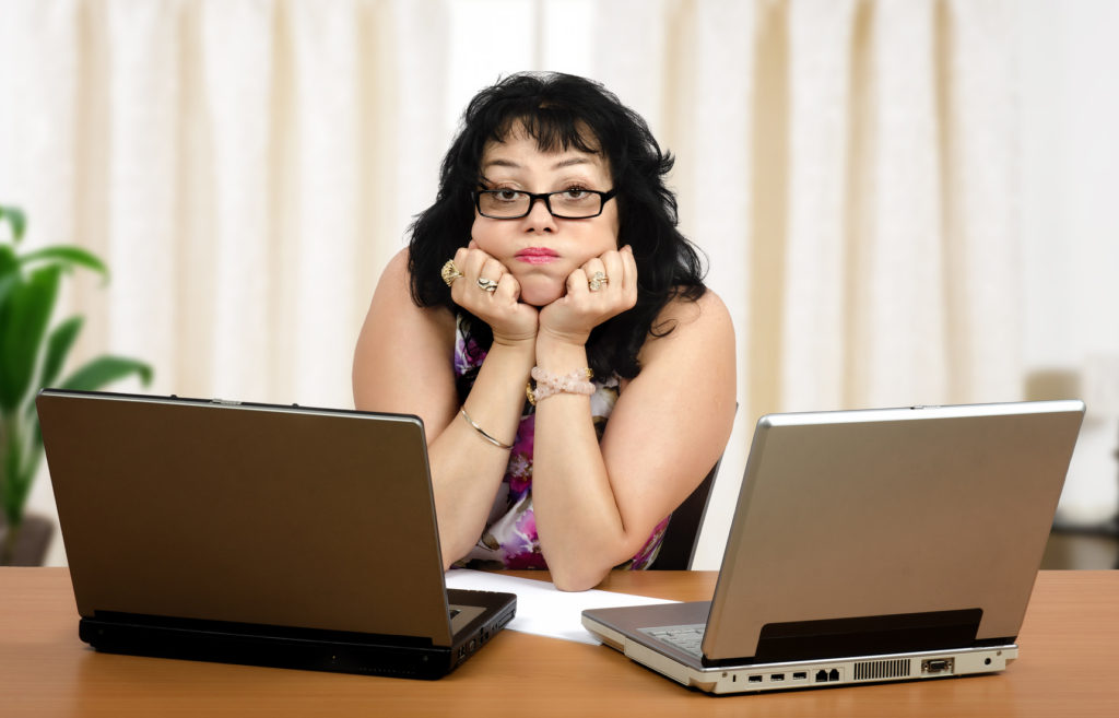 Glasses mature woman is boring on webinar on front of two laptops